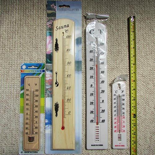 مقایسه ابعاد 4 مدل دماسنج بترتیب از راست به چپ: دماسنج پلاستیکی کوچک - دماسنج پلاستیکی بزرگ - دماسنج چوبی سونا - دماسنج چوبی کوچک